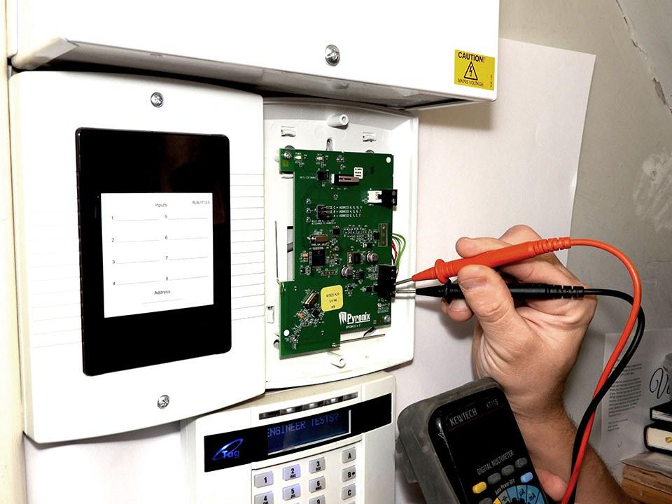 Engineer Testing Intruder Alarm